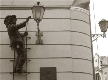 The bronze monument,that represents a lanterner on the stairs was made by the sculptor Mykhailo Kolodko.